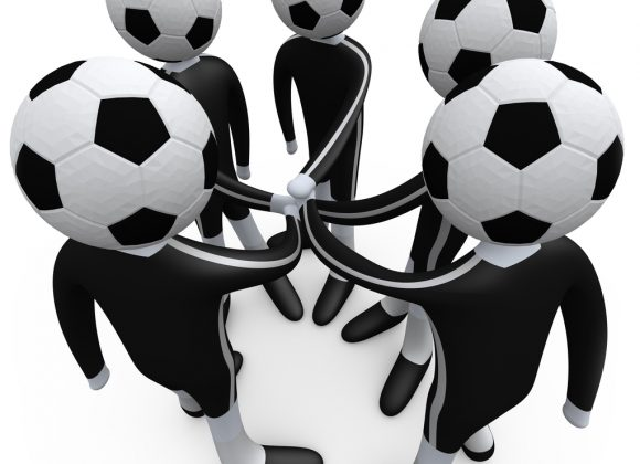Royalty-free 3d sports computer generated clipart picture of a team of soccer players with a soccer ball heads putting their hands together during a huddle.